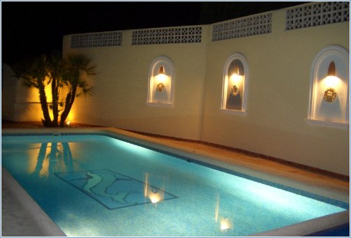 Lighted arches in wall around pool