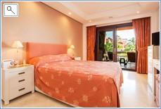 Master bedroom with doors to terrace, garden and pools
