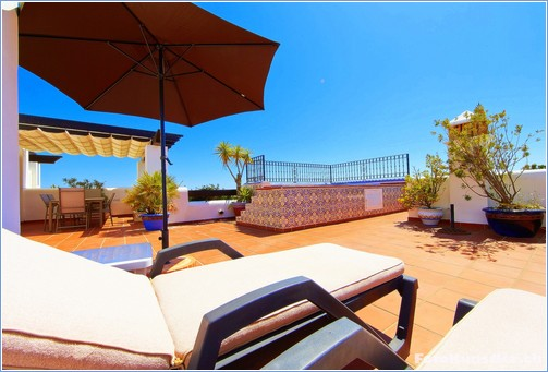 Roof terrace with jacuzzi, big dining table, chairs and beds