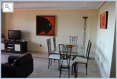 Another view of dining area with flat screen TV behind