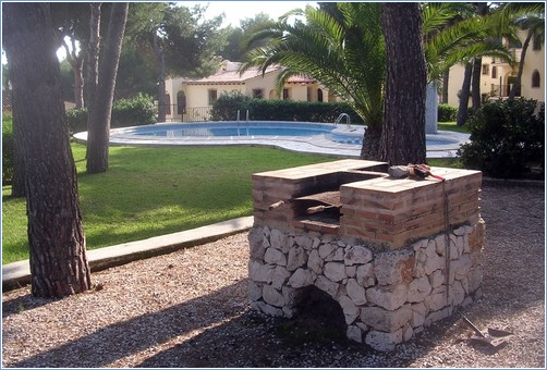 Small brick barbeque next to the smaller pool