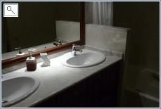Main bathroom with bath, sinks, WC