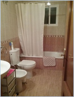Bathroom with bath shower bidet wasbasin and lit mirror
